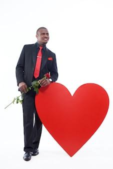Молодой африканский человек в черном люксе и красном галстуке держит красную розу, подарок на день святого валентина