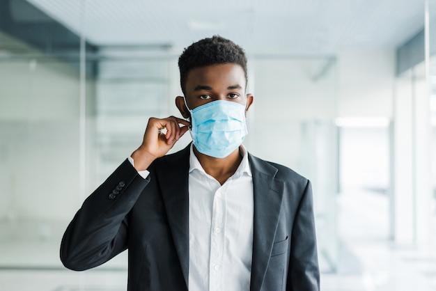 オフィスで彼の顔に医療マスクの若いアフリカ人