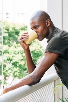 Young african man leaning on railing drinking the coffee