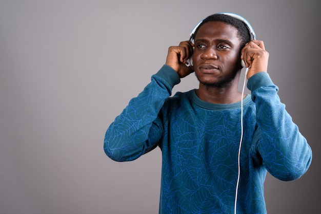 Young african man listening to music on gray
