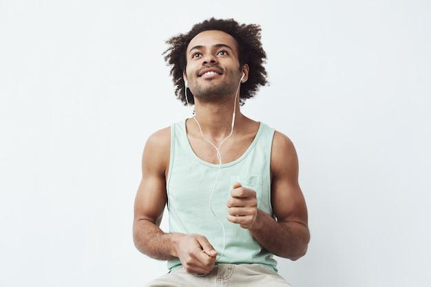Молодой африканский человек слушает онлайн потоковую музыку в проводных наушниках танцует, делая вид, что барабанит, наслаждаясь басом