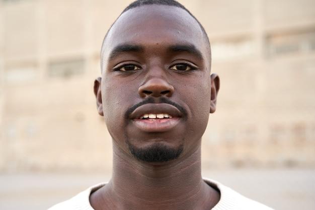 屋外に立っているカメラを見ている若いアフリカ人