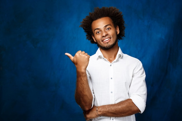 Young african man pointing finger in side over blue wall.