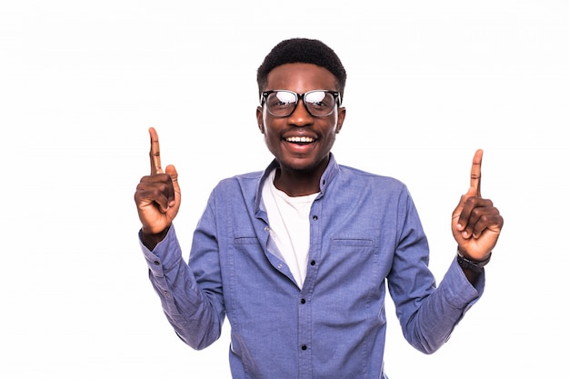 Young african man pointing up over white wall