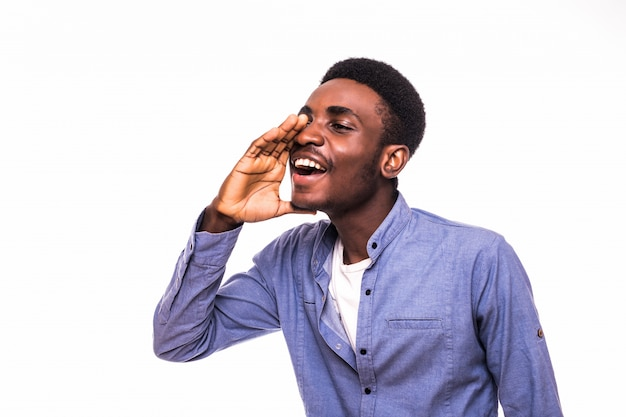 Young african man screaming out loud isolated on white wall
