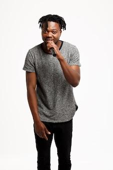 Giovane uomo africano che canta in microfono su bianco.