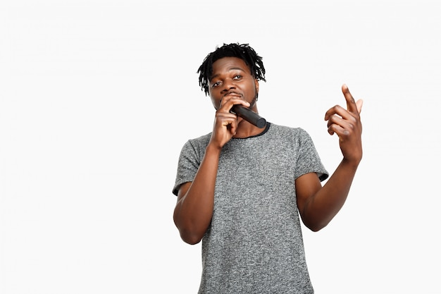 Young african man singing in microphone on white.