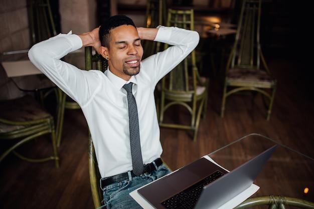 노트북과 커피 숍에 앉아 젊은 아프리카 남자, 학생 유행 옷을 입고
