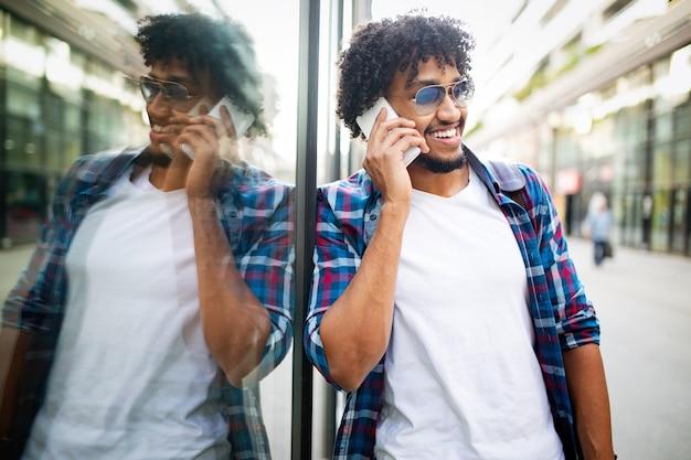 웃으면서 밖에서 휴대폰 통화를 하는 젊은 아프리카 남자