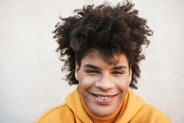 街の屋外カメラで笑っている若いアフリカ人-顔に焦点を当てる