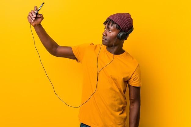 Молодой африканец, стоящий на фоне желтого пространства в шляпе, слушает музыку по телефону