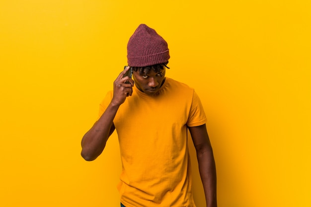 Young african man standing against a yellow background wearing a hat and using a phone