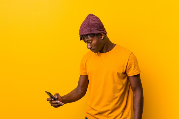 Young african man standing against a yellow wall wearing a hat and using a phone