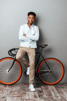 Young african man standing over grey wall with bicycle.