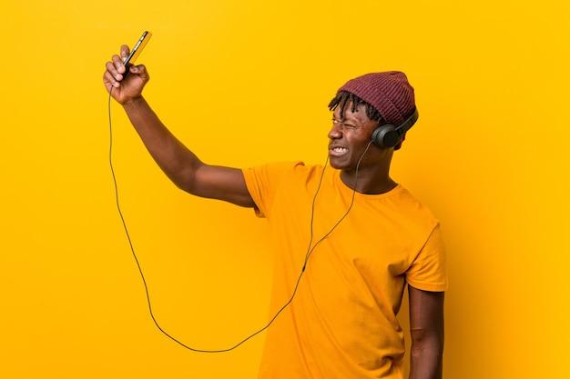 전화로 음악을 듣고 모자를 쓰고 노란색에 서있는 젊은 아프리카 남자