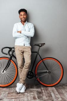 自転車で灰色の壁の上に立っている若いアフリカ人。