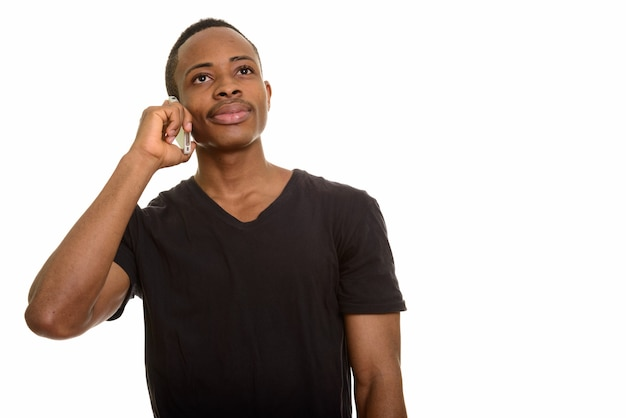 考えながら携帯電話で話している若いアフリカ人