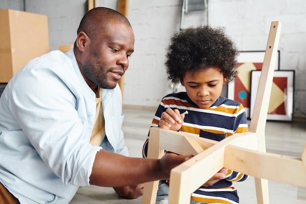 愛らしい幼い息子に、木製の椅子を組み立てて細部を修正する方法を釘で教えながら、彼を助けている若いアフリカ人男性
