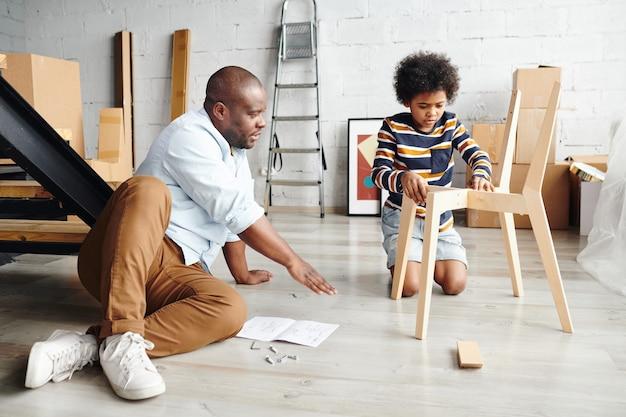 彼らの新しいアパートや家の床に座っている間、彼のかわいい幼い息子に木製の椅子を組み立てる方法を教える若いアフリカ人