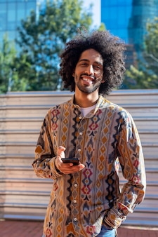 Young african man using his smartphone with smile while standing outdoors in sunny day