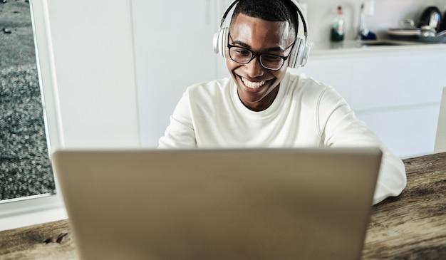 Молодой африканский человек с помощью портативного компьютера в наушниках дома - сосредоточиться на лице