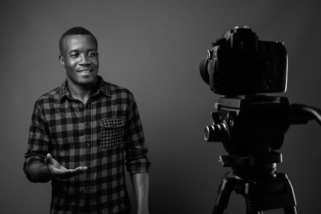 灰色の壁に市松模様のシャツを着ている間、若いアフリカ人がブログを書いています。黒と白