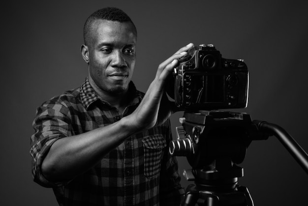 Young african man vlogging while wearing checkered shirt against gray wall. black and white