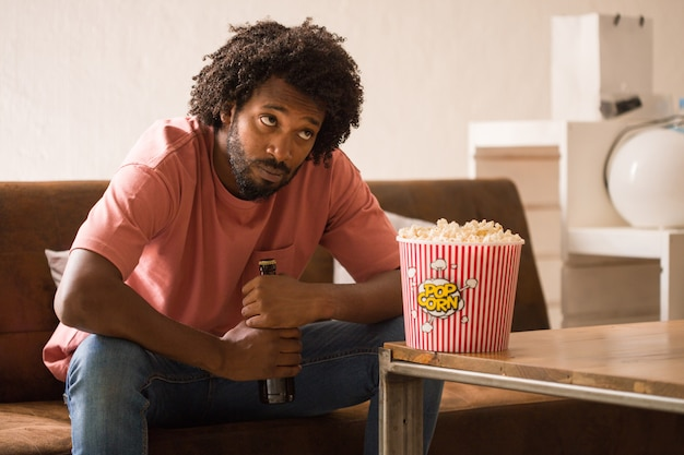 Young african man watching television, he is bored, holding a popcorn bucket.