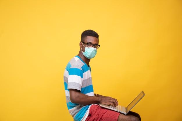 Молодой африканский человек в маске и очках с помощью ноутбука, вид сбоку