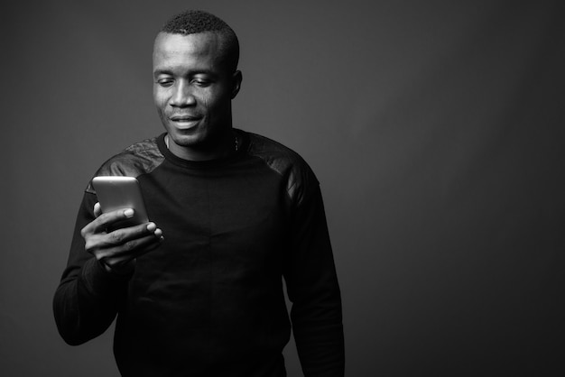Young african man wearing black long sleeved shirt against gray wall. black and white