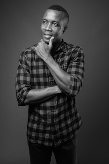 Young african man wearing checkered shirt against gray wall. black and white