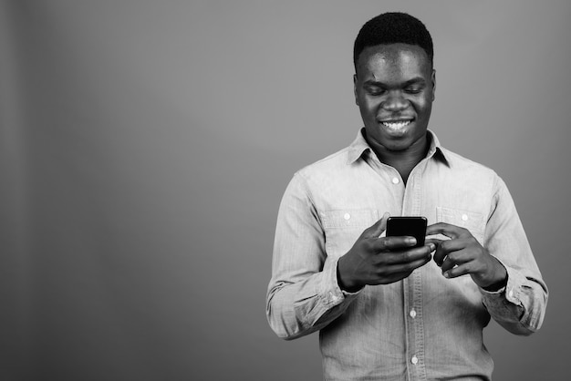 Young african man wearing denim shirt against gray wall. black and white