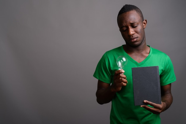 Young african man wearing green shirt on gray wall