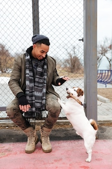 Young african man wearing hat and scarf walking with dog.