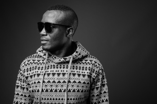 Young african man wearing hoodie and sunglasses against gray wall. black and white