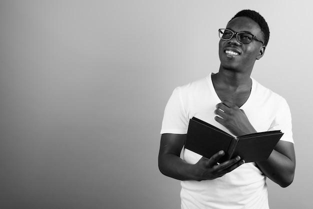 白い壁に白いシャツを着ている若いアフリカ人。黒と白