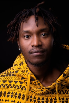 Young african man with dreadlocks on black