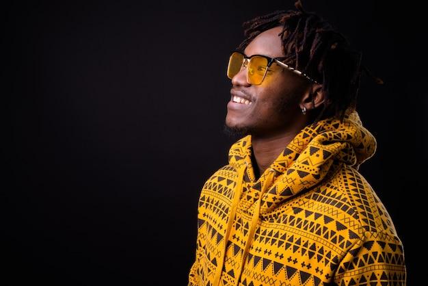 Молодой африканский мужчина с дредами на черном