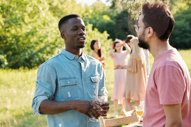 Молодой африканец с бокалом вина разговаривает с парнем смешанной расы на открытом воздухе