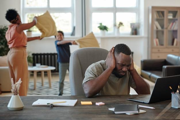 ノートパソコンの前に座って、幼い息子と遊んでいる妻とネットワークを築きながら集中しようとしている頭痛のある若いアフリカ人男性