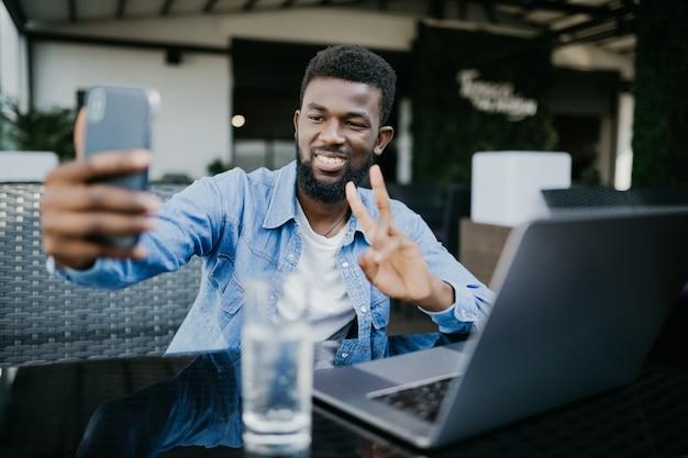 Молодой африканский мужчина с телефоном делает селфи, делая жест мира, сидя с ноутбуком в кафе