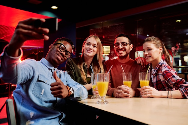 Young african man with smartphone showing thumb up while making selfie with his friends by table in cafe at leisure center