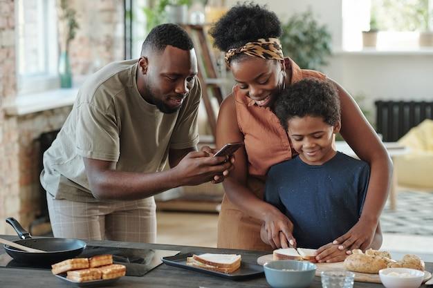 Молодой африканец со смартфоном фотографирует своего милого маленького сына, режущего хлеб для бутербродов, готовя завтрак для семьи