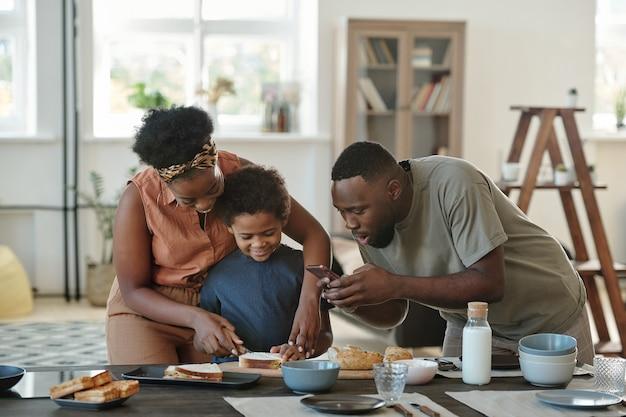 Молодой африканец со смартфоном фотографирует свою жену и их милый маленький сын, режущий хлеб для бутербродов во время приготовления завтрака