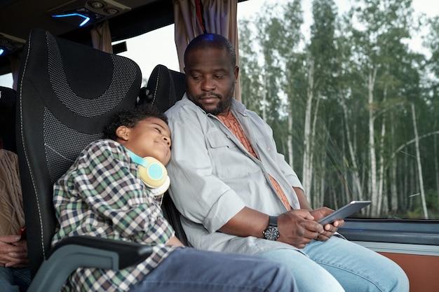 Молодой африканский человек с планшетом, глядя на своего спящего сына