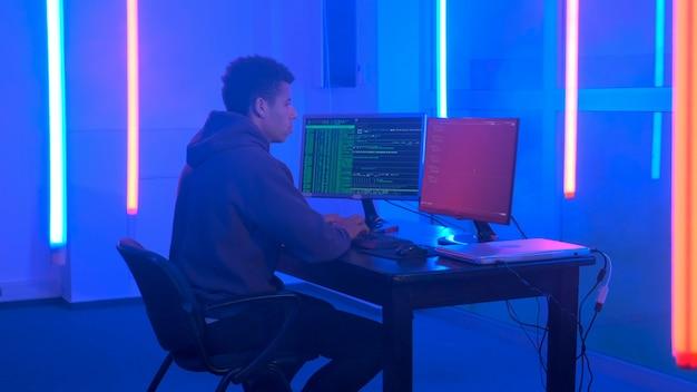 Молодой африканец пишет хакерские программы в темной комнате с неоновыми огнями, он работает на компьютере с ...