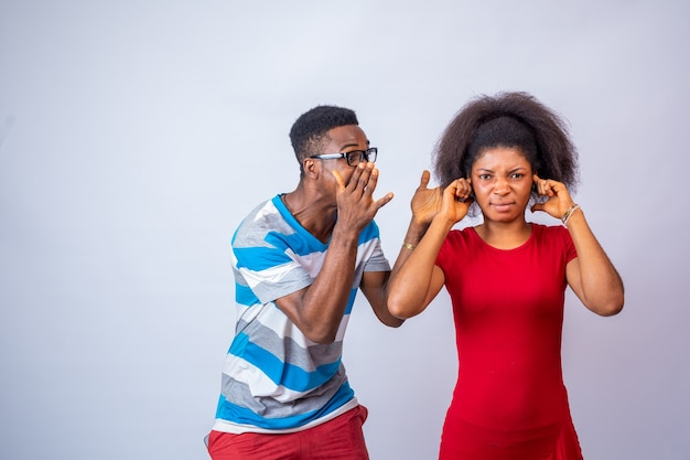 Young african man yelling at a lady who covers her ears with her finger
