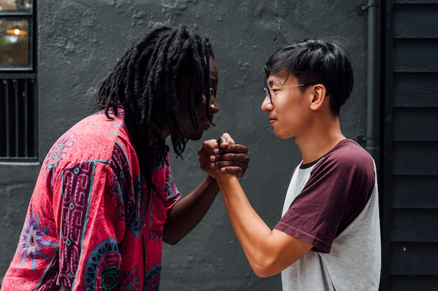 Young african man and young asian man clasp their hands