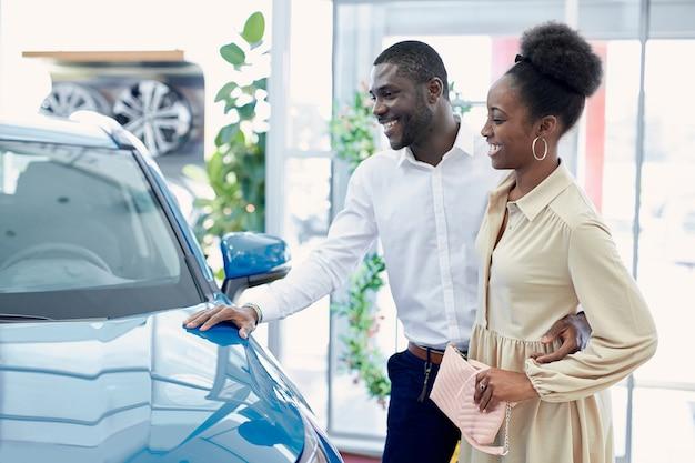 Молодая африканская супружеская пара в поисках лучшего автомобиля в автосалоне