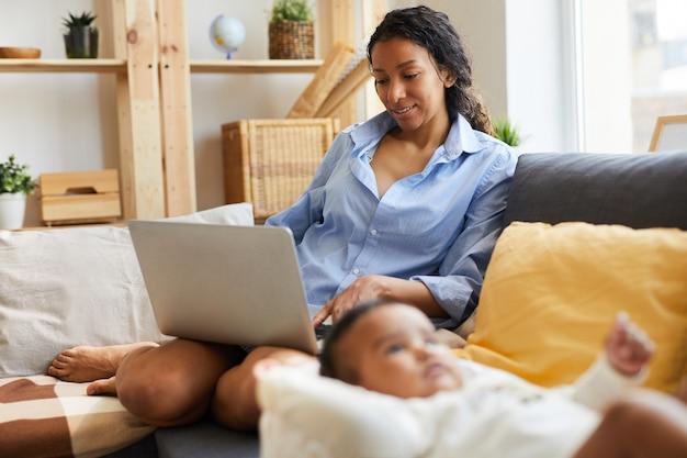 Молодая африканская мать работает на дому